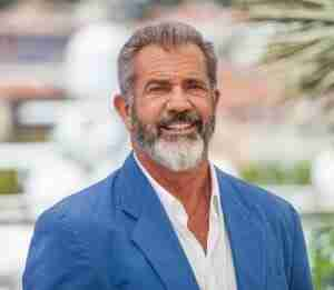 Mel Gibson in blue and white standing and smiling to camera.