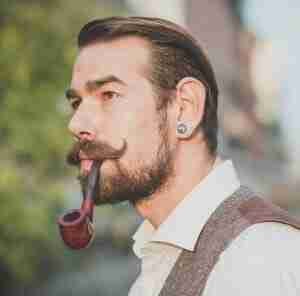 A hipster smoking pipe in street.