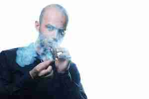 A bald serious looking guy smoking a cigar on white background.