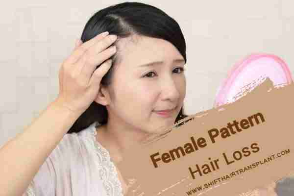 An Asian woman looking at her missed hair through pink hand mirror.