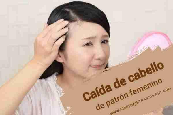 Caída de cabello de patrón femenino, Calvicie de patrón femenino, una mujer asiática que mira su cabello perdido a través del espejo de mano rosa.