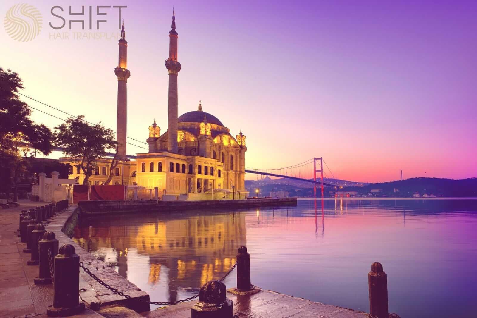 Uma vista de Ortaköy com a ponte de Bosphorus e a mesquita.