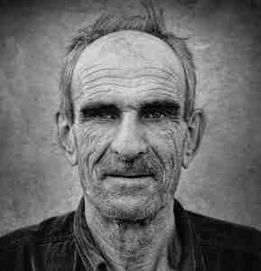 A black and white portrait of an old man with deep wrinkles.