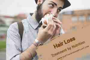 Nutritional Hair Loss Treatment, a hipster eating a sandwich outdoors.