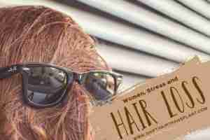 Women Stress Hair Loss, a female with her face covered with her red hair wearing a black sunglasses in front of a store.