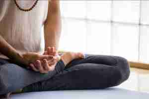 A woman wearing a black sweat pants doing meditation.