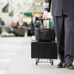 A driver dragging a valise at the airport.