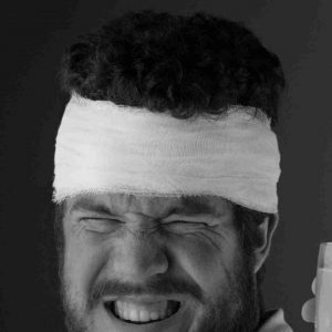 A bearded man with a head bandage on a black background.
