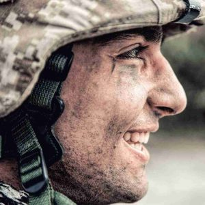 A happy solider with dirty face.